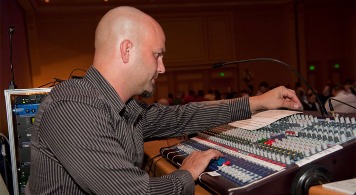 Image: Audio engineer preparing for a speaker at a Benchmarc360 organized event. Event and meeting technology and software soltuions.