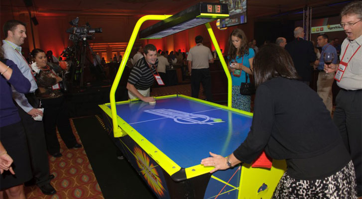 Image: Corporate employees enjoying air hockey with co-workers. Recreational activity planning and corporate team builidng activiites organized by Benchmarc360.