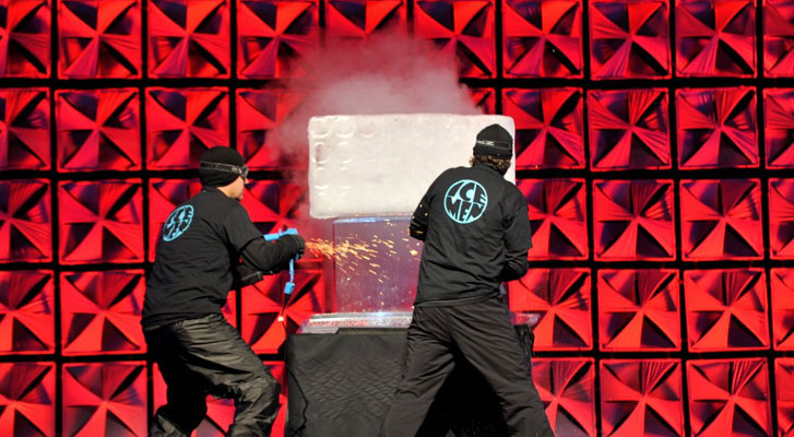 Image: Ice Men perform on stage in front of captivated corporate event audience. Event branding services by Benchmarc360.